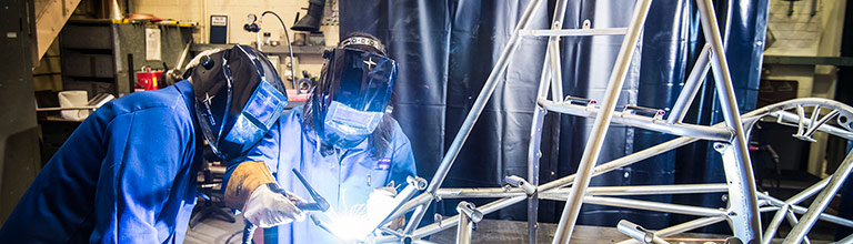 Two female students welding a frame